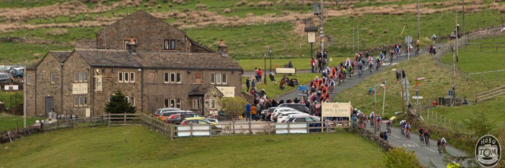 The Dog & Gun Inn, with the peloton passing, Leeming.